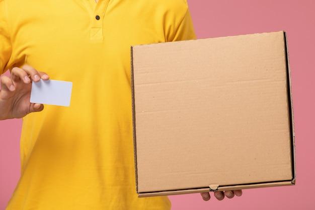 Männlicher kurier der vorderansicht in der gelben uniform, die graue karte und nahrungsmittellieferbox auf dem rosa schreibtisch hält Kostenlose Fotos
