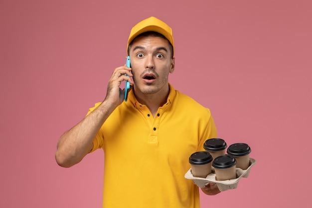 Männlicher kurier der vorderansicht in der gelben uniform, die kaffeetassen hält und am telefon überrascht auf hellrosa schreibtisch spricht Kostenlose Fotos