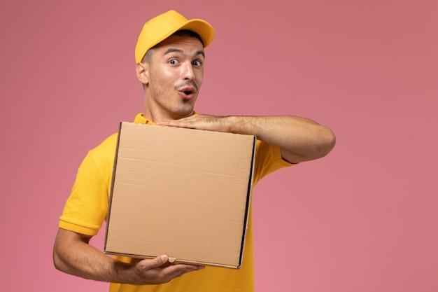 Männlicher kurier der vorderansicht in der gelben uniform, die lebensmittel-lieferbox mit lustigem ausdruck auf dem rosa schreibtisch hält Kostenlose Fotos