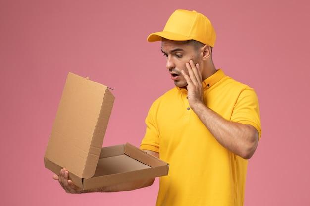 Männlicher kurier der vorderansicht in der gelben uniform, die lebensmittelabgabebox auf dem hellrosa hintergrund hält und öffnet Kostenlose Fotos
