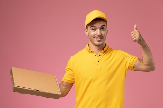 Männlicher kurier der vorderansicht in der gelben uniform, die lebensmittelabgabebox auf dem rosa hintergrund hält Kostenlose Fotos