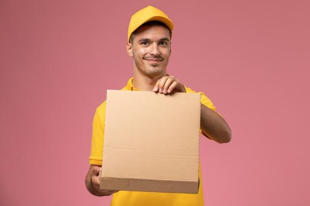 Männlicher kurier der vorderansicht in der gelben uniform, die lebensmittelabgabebox auf rosa hintergrund hält und öffnet Kostenlose Fotos