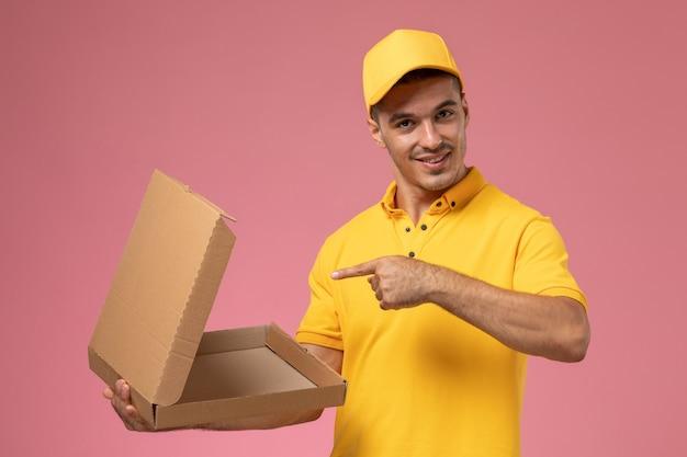 Männlicher kurier der vorderansicht in der gelben uniform, die leere essenslieferbox auf dem rosa schreibtisch hält und öffnet Kostenlose Fotos