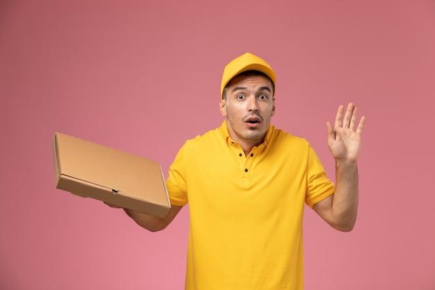 Männlicher kurier der vorderansicht in der gelben uniform, die nahrungsmittellieferbox auf rosa schreibtisch hält Kostenlose Fotos