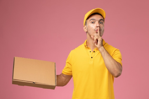 Männlicher kurier der vorderansicht in der gelben uniform, die nahrungsmittellieferbox hält und bittet, auf dem rosa hintergrund ruhig zu sein Kostenlose Fotos