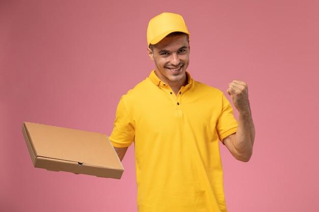 Männlicher kurier der vorderansicht in der gelben uniform, die nahrungsmittellieferbox hält und sich auf dem rosa hintergrund freut Kostenlose Fotos