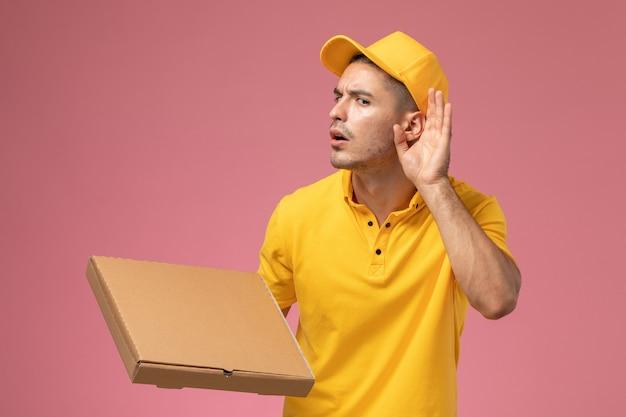 Männlicher kurier der vorderansicht in der gelben uniform, die nahrungsmittellieferbox hält und versucht, auf dem rosa hintergrund zu hören Kostenlose Fotos