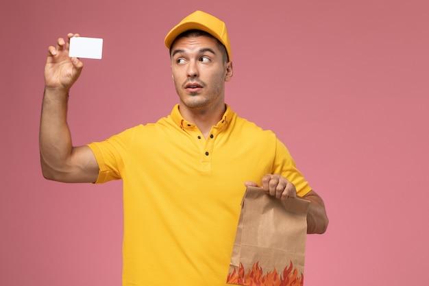 Männlicher kurier der vorderansicht in der gelben uniform, die weiße karte und lebensmittelpaket auf rosa schreibtisch hält Kostenlose Fotos
