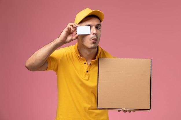 Männlicher kurier der vorderansicht in der gelben uniform, die weiße karte und nahrungsmittelbox auf dem rosa hält Kostenlose Fotos
