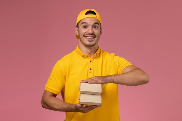Männlicher kurier der vorderansicht in der gelben uniform und im umhang, die kleine liefernahrungsmittelpakete auf dem hellrosa hintergrund halten. Kostenlose Fotos