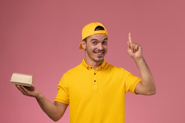 Männlicher kurier der vorderansicht in der gelben uniform und im umhang, die kleines liefernahrungsmittelpaket halten und auf hellrosa hintergrund lächeln. Kostenlose Fotos