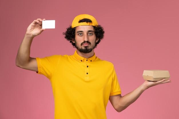 Männlicher kurier der vorderansicht in der gelben uniform und im umhang mit karte und kleinem liefernahrungsmittelpaket auf seinen händen auf dem hellrosa hintergrund. Kostenlose Fotos