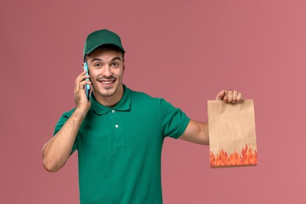 Männlicher kurier der vorderansicht in der grünen uniform, die lebensmittelpaket hält, während am telefon auf rosa spricht Kostenlose Fotos