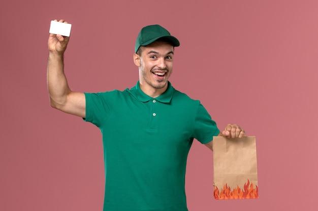 Männlicher kurier der vorderansicht in der grünen uniform, die lebensmittelpaket und karte auf dem rosa hintergrund hält Kostenlose Fotos