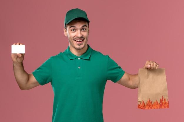Männlicher kurier der vorderansicht in der grünen uniform, die lebensmittelpaket und karte hält, die auf rosa hintergrund lächeln Kostenlose Fotos
