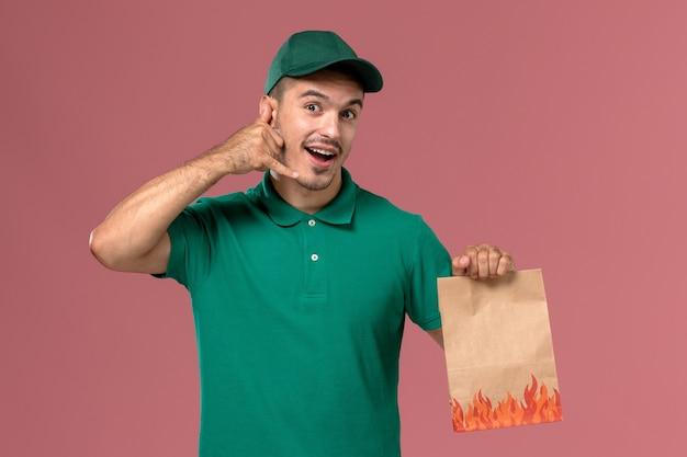 Männlicher kurier der vorderansicht in der grünen uniform, die papiernahrungsmittelpaket auf dem hellrosa hintergrund hält Kostenlose Fotos