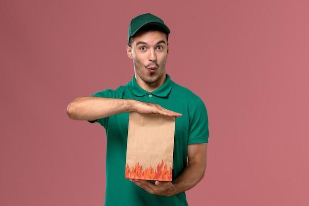 Männlicher kurier der vorderansicht in der grünen uniform, die papiernahrungsmittelpaket auf dem rosa hintergrund hält Kostenlose Fotos
