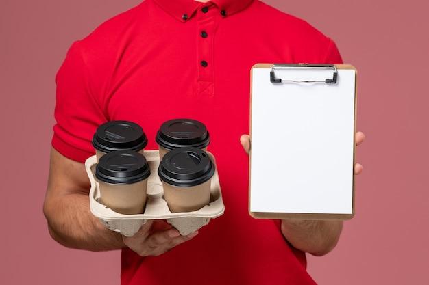 Männlicher kurier der vorderansicht in der roten uniform, die lieferkaffeetassen mit notizblock an der rosa wand hält Kostenlose Fotos