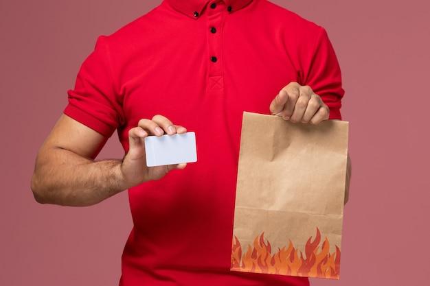 Männlicher kurier der vorderansicht in der roten uniform und im umhang, die nahrungsmittelpaket und karte auf rosa wand halten Kostenlose Fotos