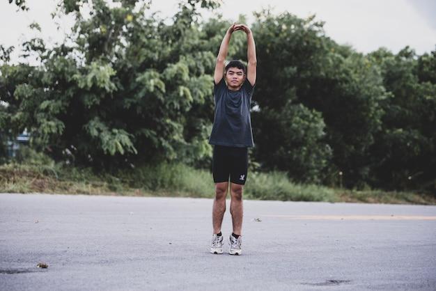 Männlicher läufer, der die übung ausdehnend tut und bereiten sich für training vor Kostenlose Fotos