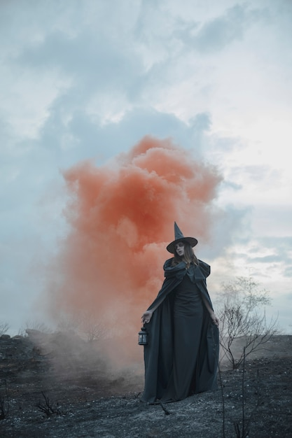 Männlicher magier in der schwarzen kleidung mit rotem nebel Kostenlose Fotos