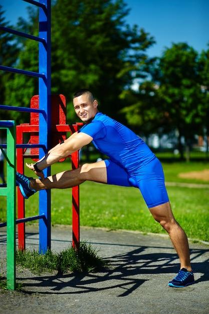 Männlicher mann hübschen gesunden glücklichen srtong athleten, der am stadtpark - eignungskonzepte an einem schönen sommertag auf horizontaler stange trainiert Kostenlose Fotos