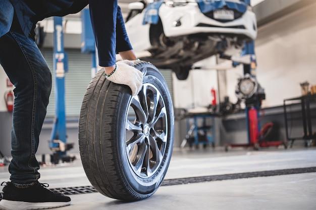 Männlicher mechanikergriff und rollenreifen an der reparatur des service-garagenhintergrundes Premium Fotos