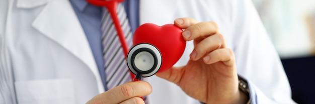 Männlicher medizinarzt, der rotes herz hält Premium Fotos