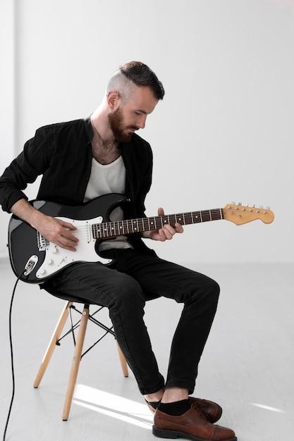 Männlicher musiker, der e-gitarre spielt Kostenlose Fotos