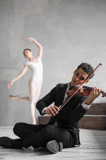 Männlicher musiker, der geige spielt und ballerina tanzt Kostenlose Fotos