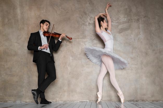 Männlicher musiker, der geige spielt, während ballerina tanzt Kostenlose Fotos