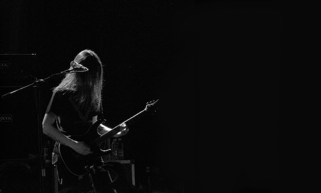 Männlicher musiker, der gitarre auf einer bühne nahe dem mikrofon in schwarzweiss spielt Kostenlose Fotos
