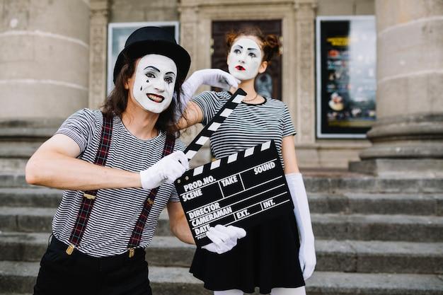 Männlicher pantomime, der clapperboard vor durchdachtem weiblichem pantomimen hält Kostenlose Fotos