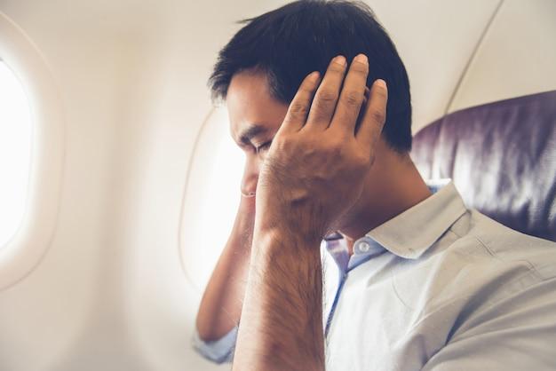 Männlicher passagier, der ohrknall im flugzeug hat Premium Fotos