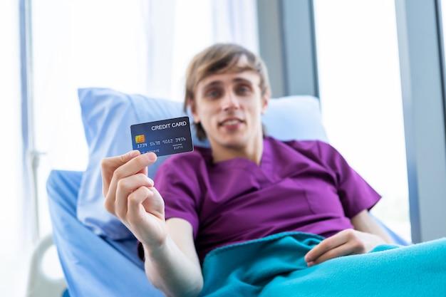 Männlicher patient, der eine kreditkarte zeigt Premium Fotos