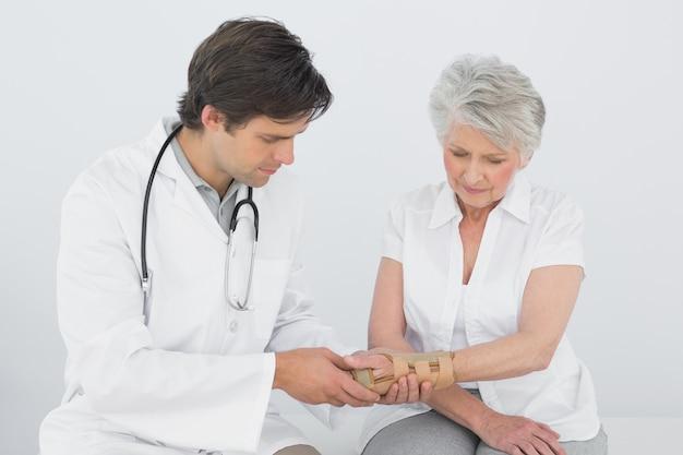 Männlicher physiotherapeut, der das handgelenk einer älteren frau überprüft Premium Fotos