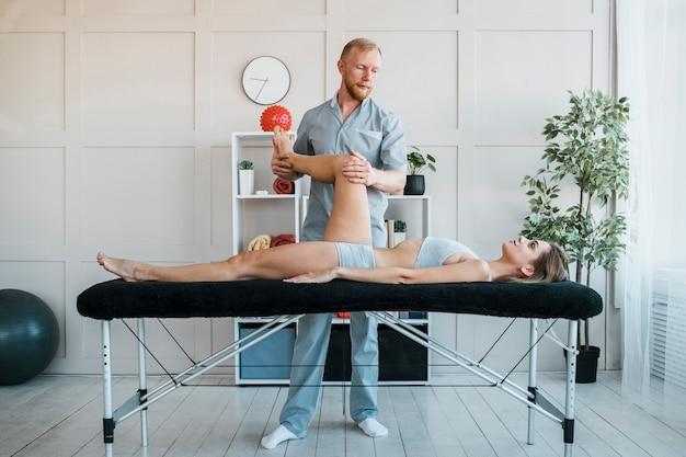 Männlicher physiotherapeut, der übungen an frau an der klinik durchführt Premium Fotos
