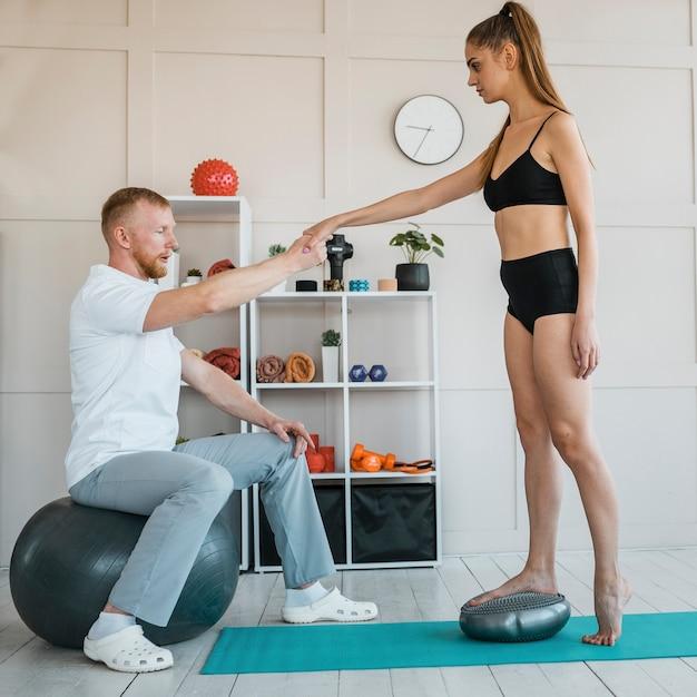Männlicher physiotherapeut während der behandlung mit einer patientin Kostenlose Fotos