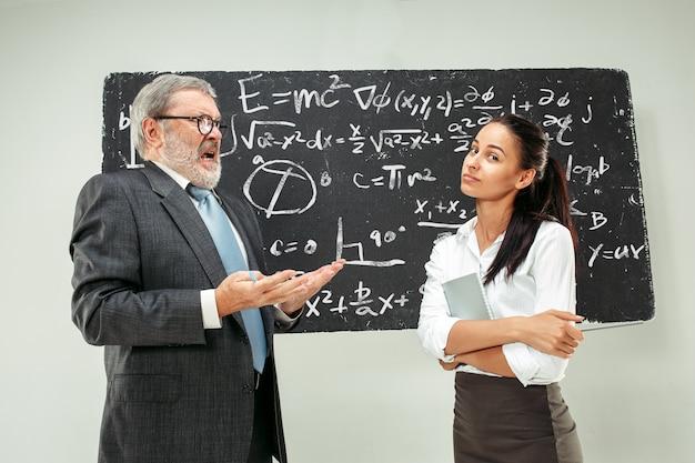 Männlicher professor und junge frau gegen tafel im klassenzimmer Kostenlose Fotos