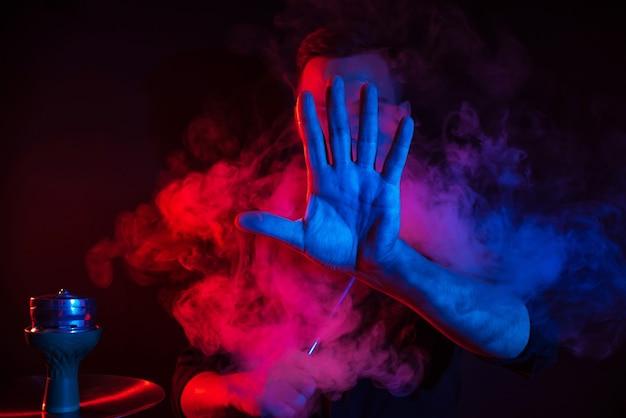 Männlicher raucher raucht eine wasserpfeife in einer shisha-bar und stößt eine rauchwolke aus, die seine hand auf einem dunklen hintergrund nach vorne legt Premium Fotos
