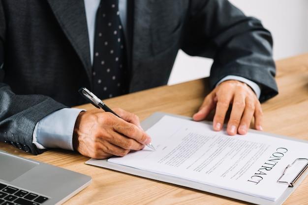 Männlicher rechtsanwalt, der den vertrag mit stift auf klemmbrett unterzeichnet Kostenlose Fotos