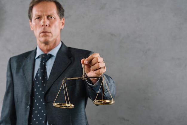 Männlicher rechtsanwalt, der goldene gerechtigkeitsskala gegen grauen strukturierten hintergrund hält Kostenlose Fotos