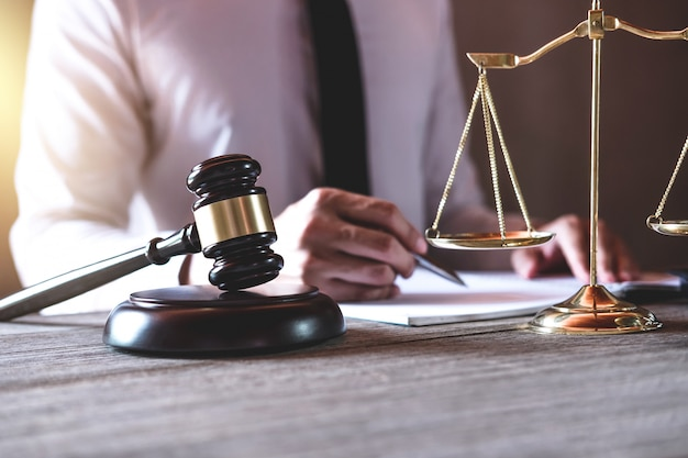 Männlicher rechtsanwalt oder richter, der mit gesetzbüchern, hammer und gleichgewicht arbeitet Premium Fotos