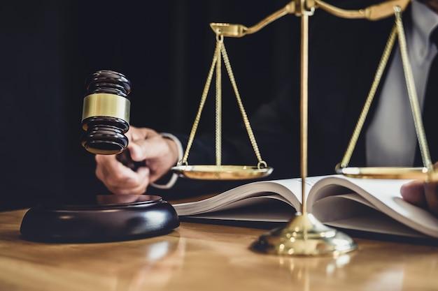 Männlicher rechtsanwalt oder richter, die mit vertragspapieren, gesetzbüchern und hölzernem hammer auf tabelle im gerichtssaal, gerechtigkeitsrechtsanwälten an der anwaltskanzlei, am gesetz und am rechtsdienstleistungskonzept arbeiten Premium Fotos
