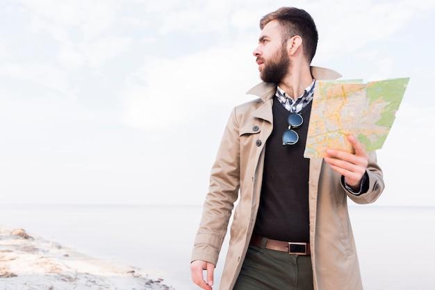 Männlicher reisender, der auf dem strand in der hand hält die karte weg schaut steht Kostenlose Fotos