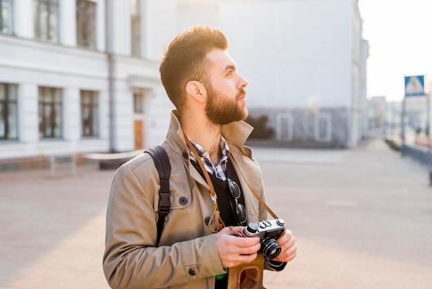 Männlicher reisender, der in der hand die weinlesekamera betrachtet die plätze in der stadt hält Kostenlose Fotos