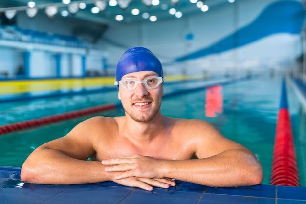 Männlicher schwimmer, der am rand des pools steht Kostenlose Fotos