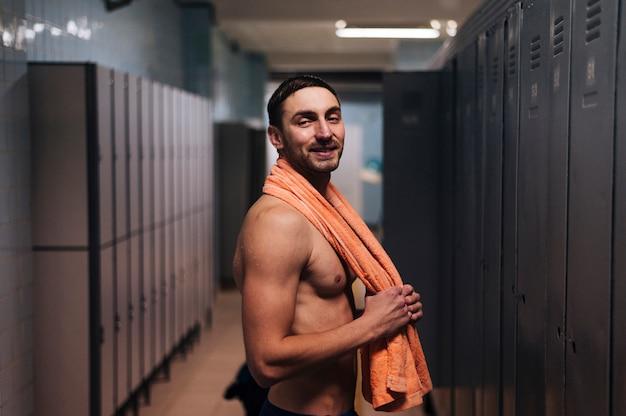 Männlicher schwimmer mit tuch im umkleideraum Kostenlose Fotos