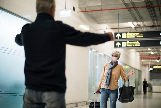 Männlicher senior, der seine frau am flughafen nach der sperrung von covid-19 abholt Kostenlose Fotos