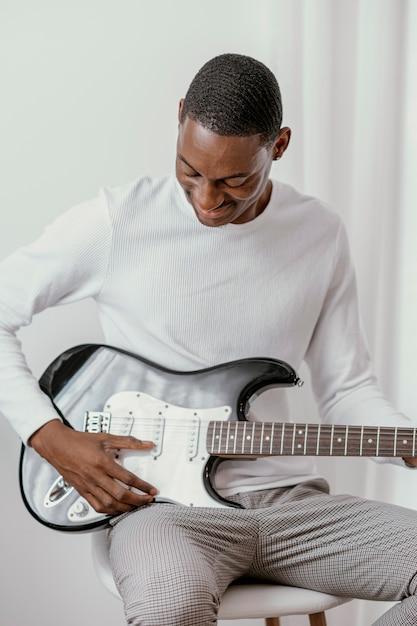 Männlicher smiley-musiker, der e-gitarre spielt Premium Fotos